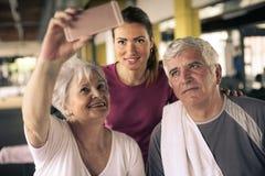 Entrenamiento de los pares en el gimnasio Gente mayor con su perso Foto de archivo libre de regalías