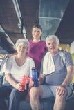 Entrenamiento de los pares en el gimnasio Gente mayor con su perso Fotografía de archivo libre de regalías