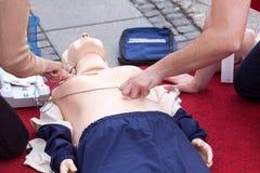 Entrenamiento de los primeros auxilios usando el dispositivo externo automatizado del defibrillator Fotografía de archivo libre de regalías