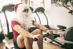 Entrenamiento de Papá Noel en aparato de remar Fotos de archivo libres de regalías