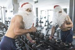 Entrenamiento de Papá Noel de la aptitud en gimnasio con pesas de gimnasia Símbolo y thum ACEPTABLES Fotos de archivo libres de regalías