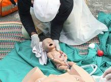 Entrenamiento de refresco para ayudar al parto recién nacido con el maniquí médico del bebé en emergencia la partera fotografía de archivo libre de regalías