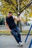 Entrenamiento de Trx Instructor del hombre en el parque que hace Excersise Entrenamiento de la aptitud Imagenes de archivo