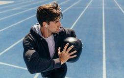 Entrenamiento del atleta con una bola de medicina en pista corriente Imagenes de archivo