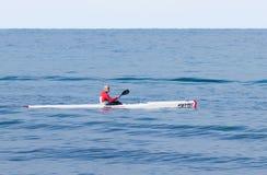 Entrenamiento del atleta el mañana del invierno del kajak en el mar cerca de la costa Imagen de archivo