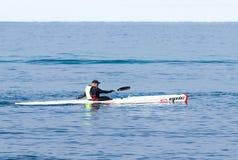 Entrenamiento del atleta el mañana del invierno del kajak en el mar cerca de la costa Imagen de archivo libre de regalías