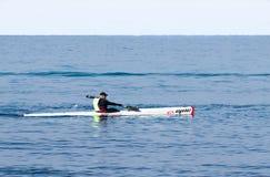 Entrenamiento del atleta el mañana del invierno del kajak en el mar cerca de la costa Imagenes de archivo