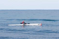 Entrenamiento del atleta el mañana del invierno del kajak en el mar cerca de la costa Fotos de archivo