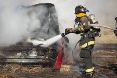 Entrenamiento del bombero en un coche ardiente Imágenes de archivo libres de regalías