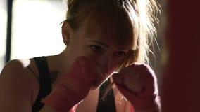 Entrenamiento del boxeador de la mujer profesional antes del partido importante, saco de arena almacen de video