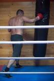 Entrenamiento del boxeador del retroceso en un saco de arena Foto de archivo libre de regalías