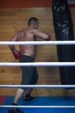 Entrenamiento del boxeador del retroceso en un saco de arena Imagenes de archivo