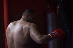 Entrenamiento del boxeador del retroceso en un saco de arena Fotos de archivo libres de regalías