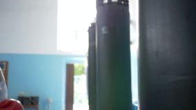 Entrenamiento del boxeador en el club de deportes, muchacha atlética que lleva los guantes rojos que baten ascendente cercano del metrajes