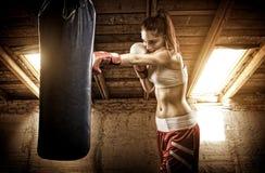 Entrenamiento del boxeo de la mujer joven en el ático Foto de archivo libre de regalías