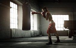 Entrenamiento del boxeo de la mujer joven en un edificio viejo