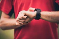 Entrenamiento del corredor y usar el reloj elegante del monitor del ritmo cardíaco Imagen de archivo libre de regalías