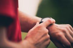 Entrenamiento del corredor y usar el reloj elegante del monitor del ritmo cardíaco Foto de archivo libre de regalías