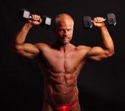Entrenamiento del culturista con pesas de gimnasia Fotos de archivo