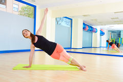 Entrenamiento del ejercicio de la curva del lado de la mujer de Pilates en el gimnasio Foto de archivo libre de regalías