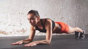 Entrenamiento del ejercicio del tablón para el entrenamiento de la mujer de la aptitud en el gimnasio Cámara lenta almacen de video
