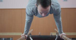 Entrenamiento del gimnasta en barrases paralelas en el gimnasio metrajes