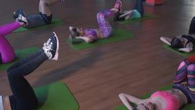 Entrenamiento del grupo de personas en un gimnasio - el instructor personal y las personas juguetonas en una aptitud clasifican metrajes