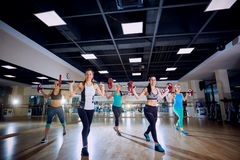 entrenamiento del grupo Muchachas que hacen ejercicios con una barra en el gimnasio Foto de archivo libre de regalías