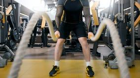 Entrenamiento del hombre con la cuerda de la batalla en club de fitness fotografía de archivo libre de regalías