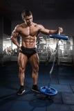 Entrenamiento del hombre del levantamiento de pesas del atleta con la barra en gimnasio fotografía de archivo libre de regalías