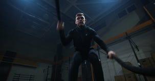 Entrenamiento del hombre joven con la cuerda de la batalla almacen de metraje de vídeo
