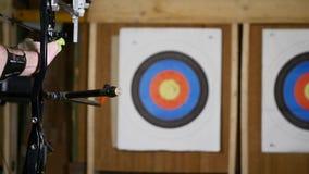 Entrenamiento del hombre joven en el tiro al arco con el arco y las flechas, gente, deportes metrajes