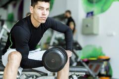 Entrenamiento del hombre joven en un gimnasio Fotos de archivo libres de regalías