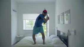 Entrenamiento del hombre joven para jugar al tenis que se coloca en la cama en la habitación cómoda Forma de vida activa Mudanza  almacen de metraje de vídeo