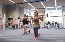 Entrenamiento del hombre joven y de la mujer con el barbell en gimnasio Foto de archivo