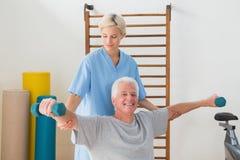 Entrenamiento del hombre mayor con su terapeuta Imágenes de archivo libres de regalías