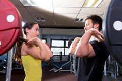 Entrenamiento del hombre y de la mujer del Barbell en el gimnasio de la aptitud Foto de archivo libre de regalías
