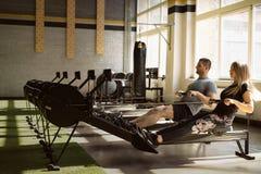 Entrenamiento del hombre y de la mujer en los aparatos de remar en gimnasio junto Fotos de archivo libres de regalías