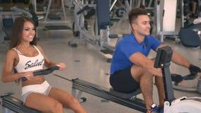 Entrenamiento del hombre y de la mujer en un aparato de remar en gimnasio almacen de metraje de vídeo