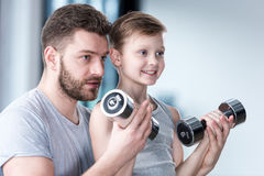 Entrenamiento del muchacho con pesas de gimnasia así como el coche foto de archivo