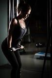 Entrenamiento del peso de la mujer en la gimnasia El ejercicio encendido tira hacia abajo la máquina del peso Mujer que hace tiró Foto de archivo
