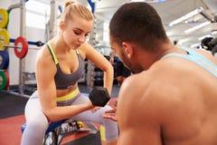 Entrenamiento del peso de la mujer en un gimnasio que consigue consejo de un instructor Foto de archivo libre de regalías
