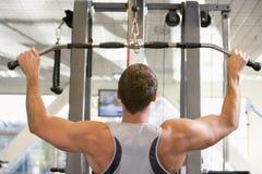 Entrenamiento del peso del hombre en la gimnasia Fotos de archivo libres de regalías