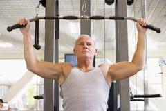 Entrenamiento del peso del hombre en la gimnasia Fotografía de archivo libre de regalías