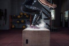 Entrenamiento del salto de la caja en el primer apto del gimnasio de la cruz fotografía de archivo