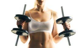 Entrenamiento deportivo de la mujer con las pesas de gimnasia aisladas en blanco Concepto del deporte, de la salud y de la aptitu Imágenes de archivo libres de regalías