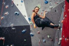 Entrenamiento deportivo de la mujer joven en un gimnasio que sube colorido Muchacha libre del escalador que sube para arriba inte Foto de archivo libre de regalías