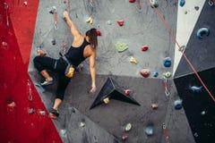 Entrenamiento deportivo de la mujer joven en un gimnasio que sube colorido Muchacha libre del escalador que sube para arriba inte Fotografía de archivo libre de regalías