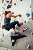 Entrenamiento deportivo de la mujer joven en un gimnasio que sube colorido Muchacha libre del escalador que sube para arriba inte Fotos de archivo