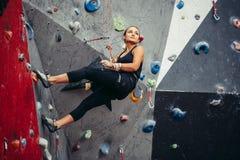 Entrenamiento deportivo de la mujer joven en un gimnasio que sube colorido Muchacha libre del escalador que sube para arriba inte Imagen de archivo